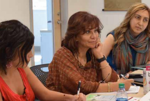 Three female participants of the workshop listening and taking notes